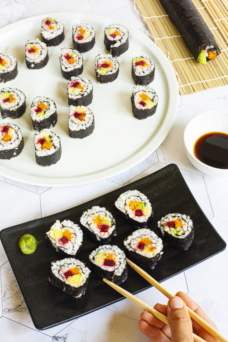 7 sushi rolls on a black plate. The rolls have black cover and white inside with purple yellow and green in the middle. A large white plate at the back with more rolls.