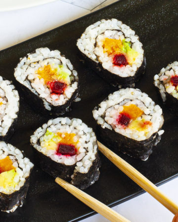 6 sushi rolls on a black plate. The rolls have black cover and white inside with purple yellow and green in the middle.