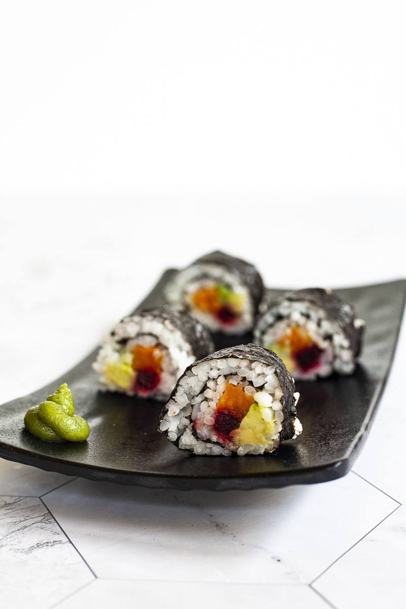 4 sushi rolls on a black plate. The rolls have black cover and white inside with purple yellow and green in the middle.