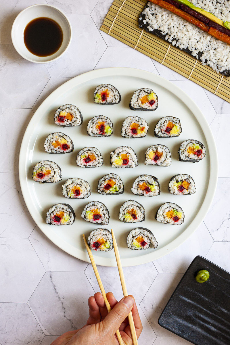 Numerous sushi rolls on a large round white plate. The rolls have black cover and white inside with purple yellow and green in the middle.
