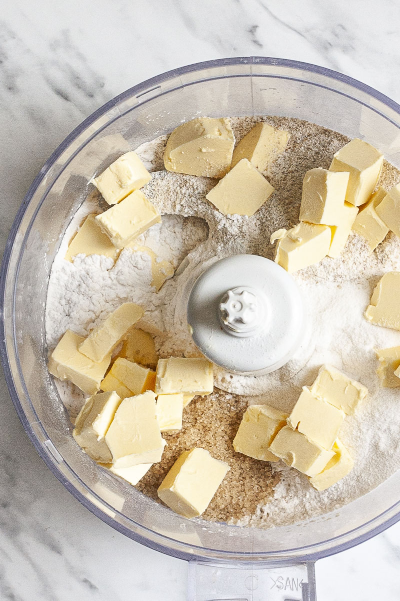 Open food processor from above with the ingredients of vegan gluten-free pie crust, different white and brown powders and yellow cubes of butter