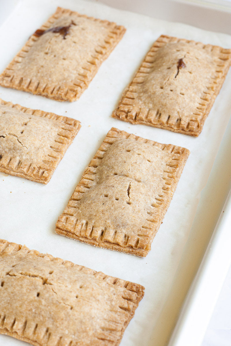 Baked pop tarts, rectangle-shaped pillow-like cookies on a white parchment paper
