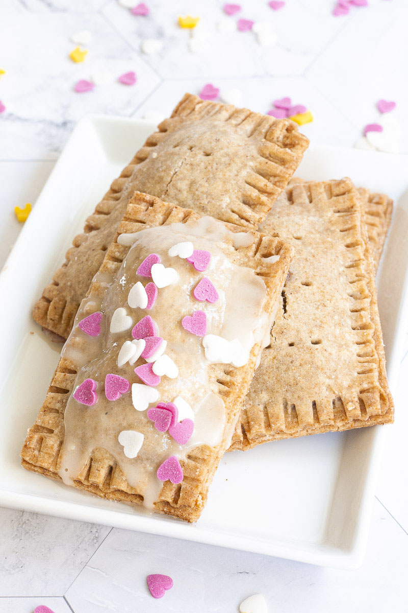 4 pop tarts, rectangle-shaped pillow-like cookies on a white plate. One has white glaze and white and pink small hearts on the top.