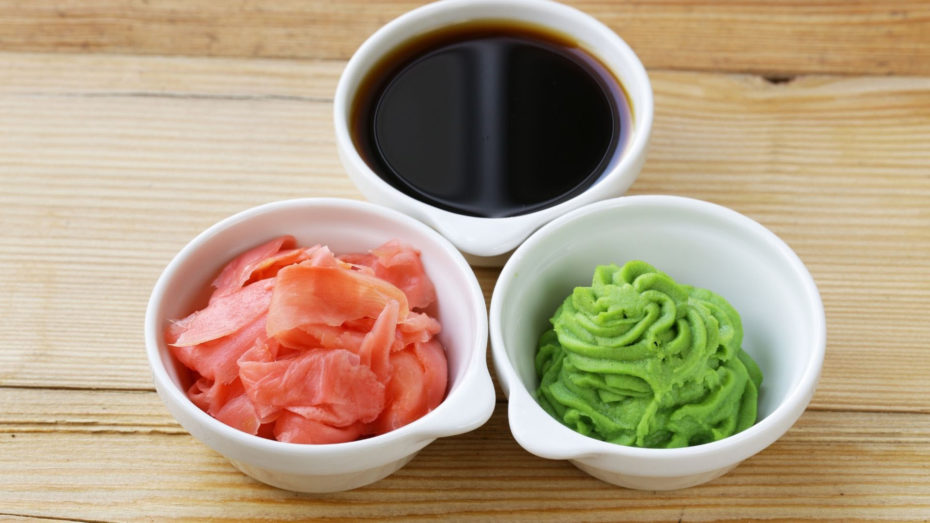 3 small white bowls. One with black liquid, one with pink slices, and one with green paste.
