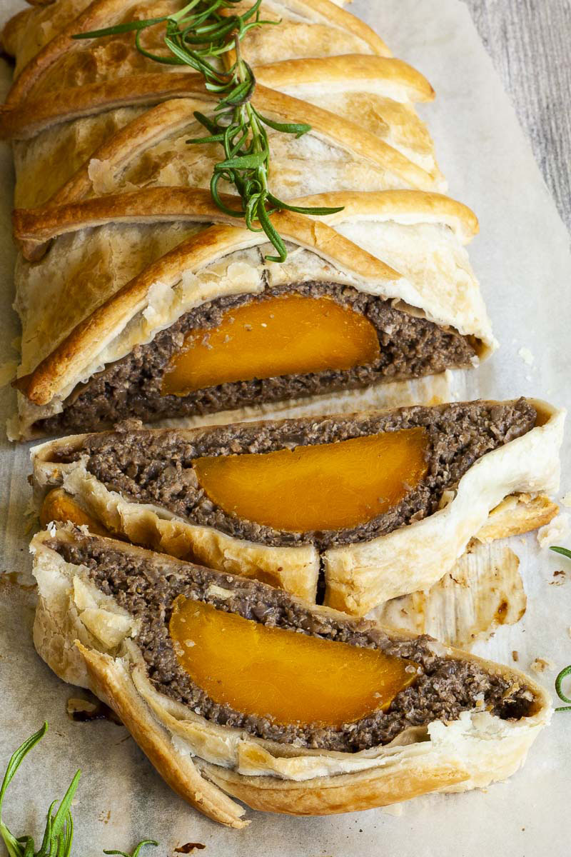 2 slices of vegan wellington on the side. Yellow squash with brown puree around wrapped in a pastry shell. Green herbs are around.