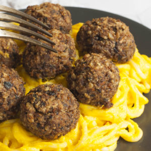 Several mushroom meatballs on top of spaghetti with yellow creamy sauce served on a black plate. A fork is taking on meatballs from the middle.