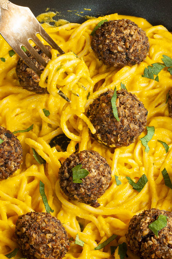 Yellow pasta sauce in a frying pan topped with mushroom meatballs.