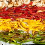 Yellow, red and green bell peppers slices seasoned with red spices on a white parchment paper