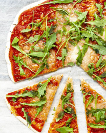 Gluten-free pizza with tomato sauce, melted cheese and fresh arugula on a white parchment paper from above. 3 slices have been cut and pulled apart.