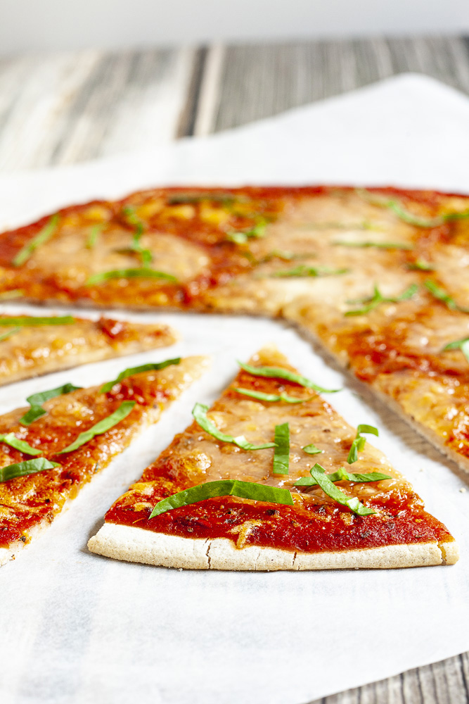 Gluten-free pizza with tomato sauce, melted cheese and fresh basil on a white parchment paper. 3 slices are cut and pulled apart.