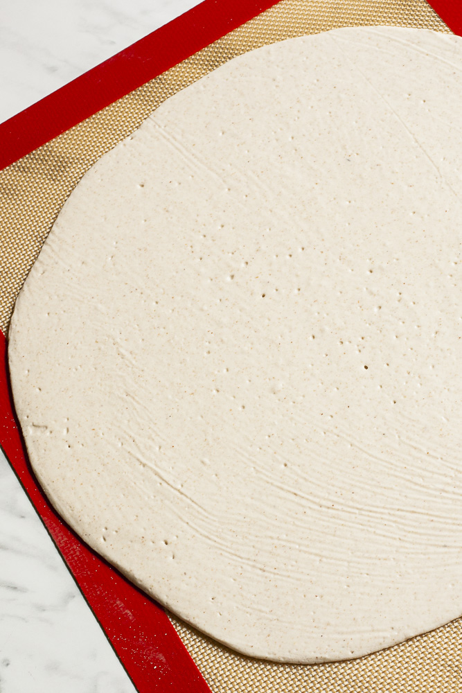 Large thin pizza crust rolled out on top of a red brown silicone rolling mat
