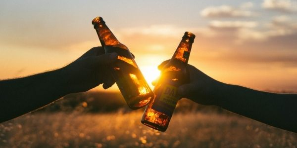 Two hands holding beer bottles making a toast