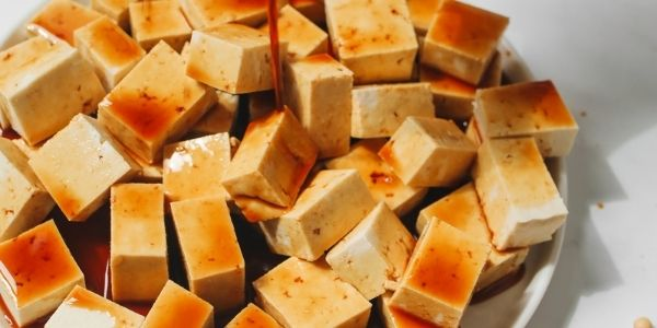Brown sauce is poured over tofu cubes up close