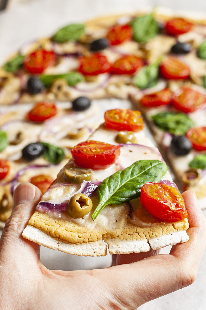 A hand is holding a slice of baked pizza with melted cheese, cherry tomatoes, purple onion slices, green olives and fresh basil leaves the remaining of the pizza is at the background.