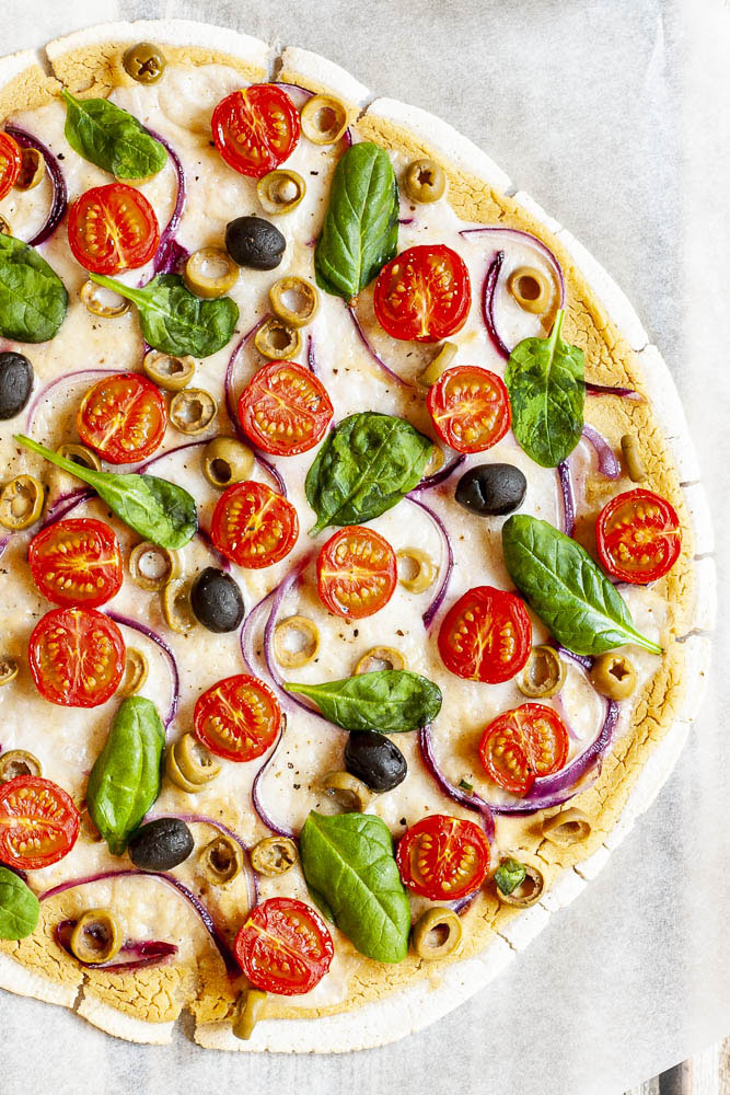 Baked pizza crust from above on white parchment paper topped with hummus, cherry tomatoes, purple onion slices, green and black olives, melted cheese and fresh basil leaves.