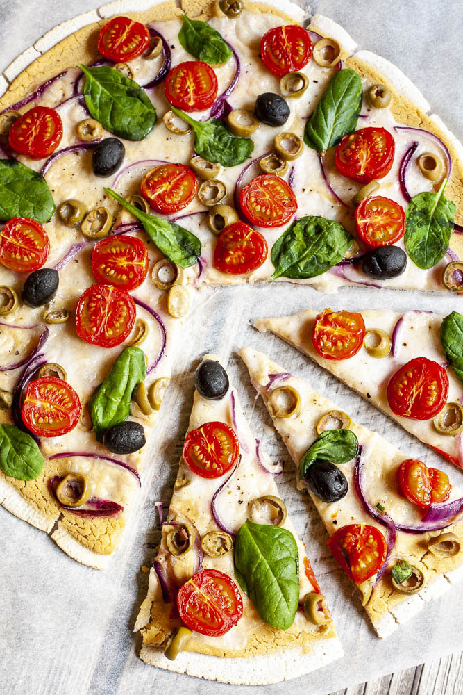 Baked and sliced pizza from above on white parchment paper topped with hummus, cherry tomatoes, purple onion slices, green and black olives, melted cheese and fresh basil leaves.