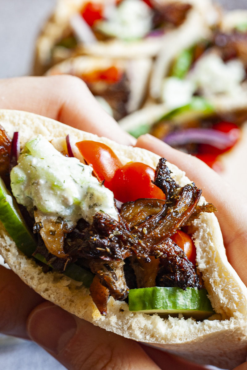 A pita pocket in a hand stuffed with crispy brown shredded oyster mushroom, tomato and cucumber slices andwhite-green tzaztziki sauce