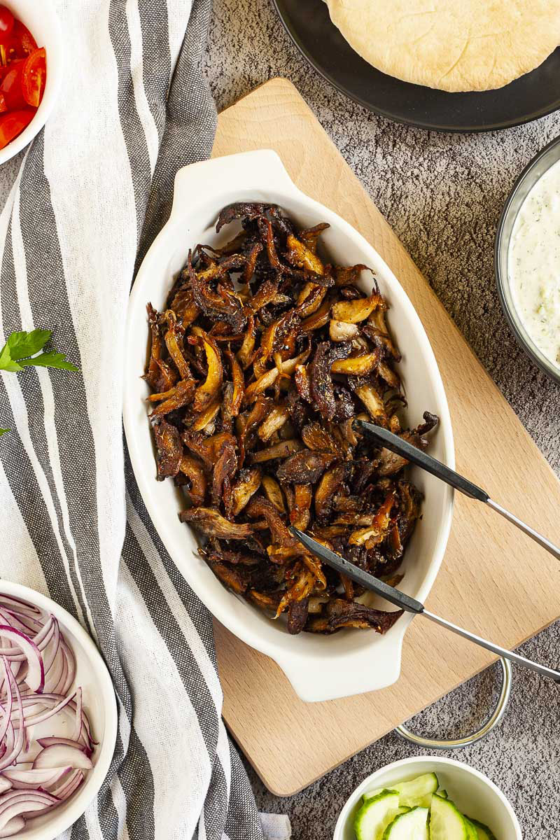 White serving bowl full of dark brown crispy shredded oyster mushrooms. Other ingredients are around in small bowls like purple onion, tomato and cucumber slices and pita bread.