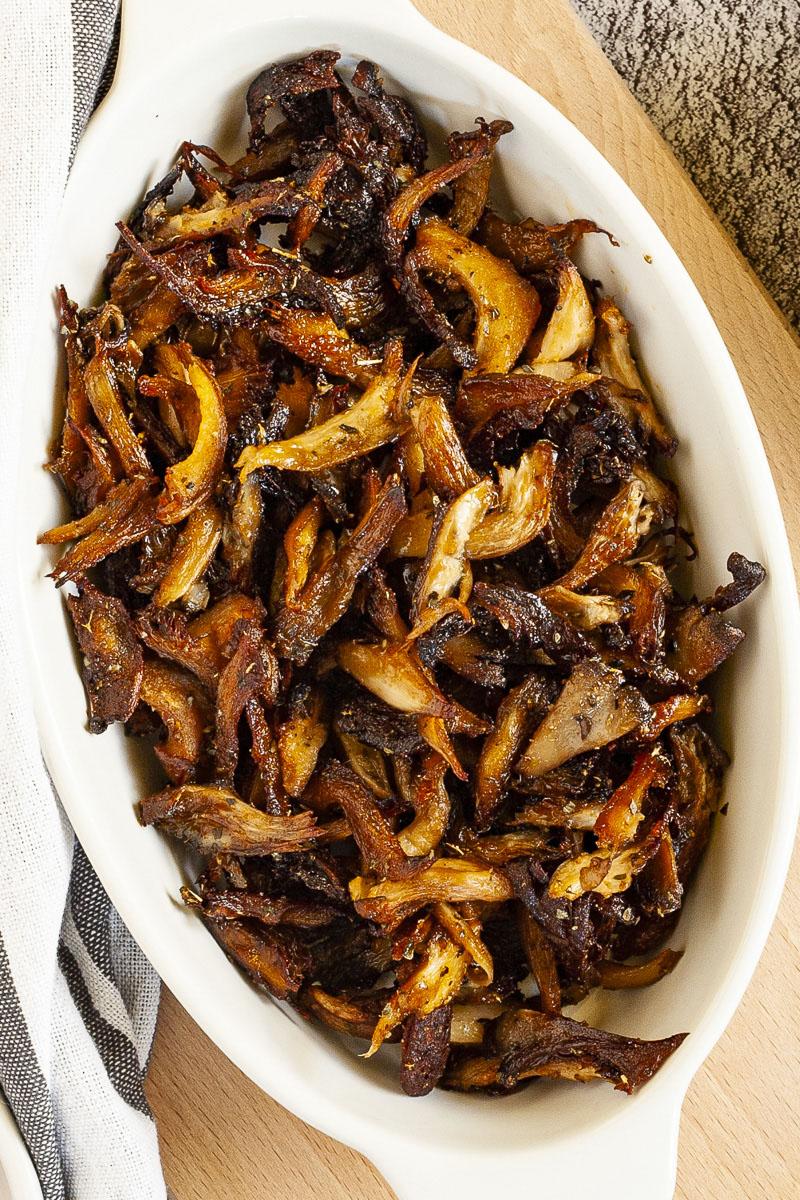 White serving bowl full of dark brown crispy shredded oyster mushrooms