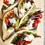 Several pita pocket on a white serving tray stuffed with crispy brown shredded oyster mushroom, tomato and cucumber slices andwhite-green tzaztziki sauce