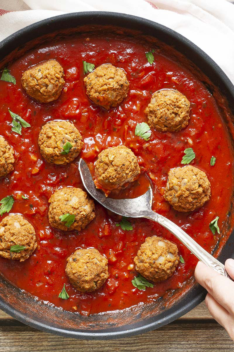 A skillet from above with several baked brown meatballs in bright red sauce and chopped green herbs. A spoon is taking one ball from the middle.
