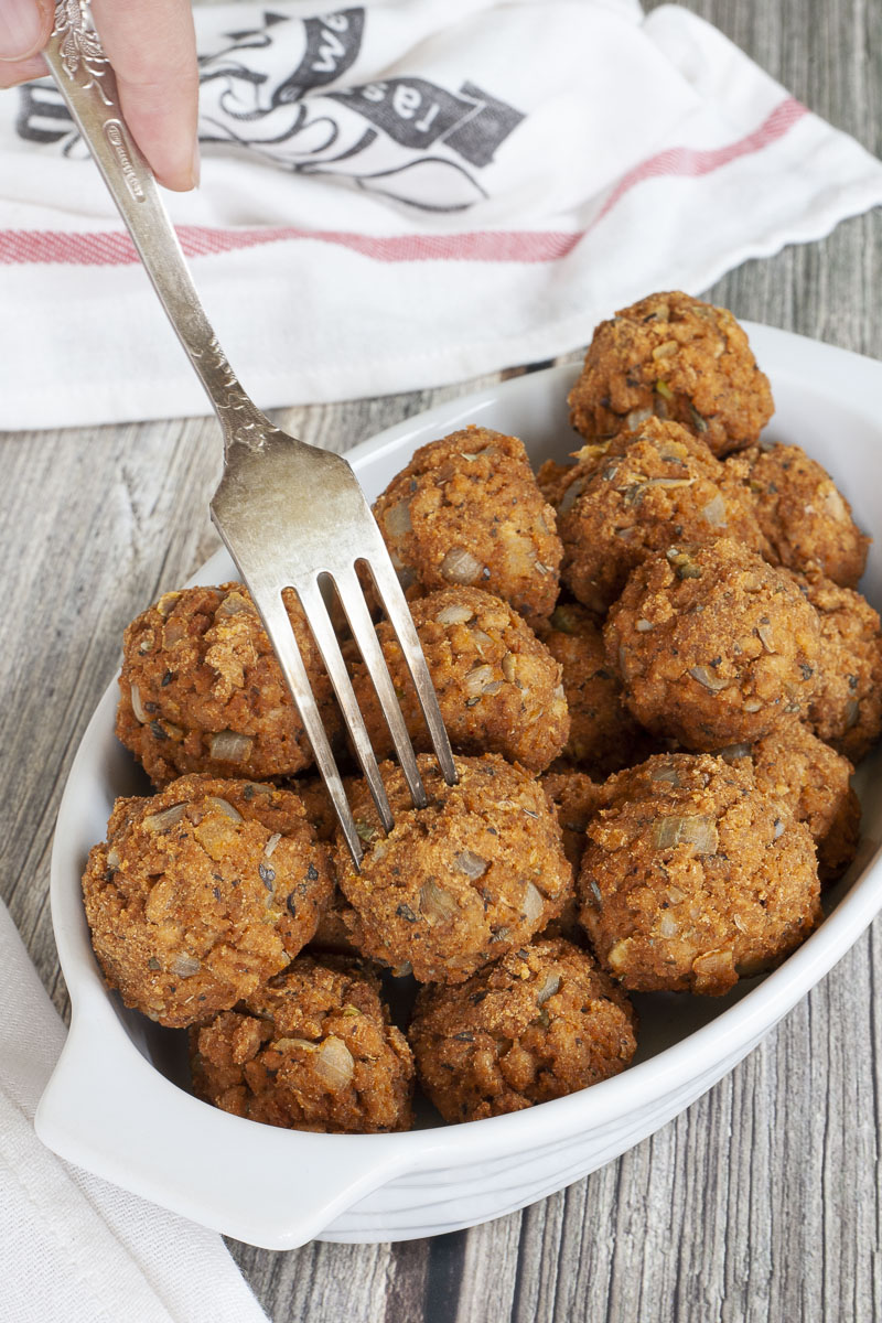 A white serving bowl full of baked brown vegan tvp meatballs. A fork is taking a ball from the middle.