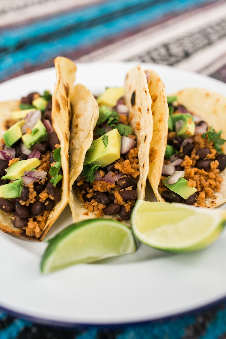 White plate with 3 tacos filled with brown crumbles, black beans, avocado chunks and lime wedges.