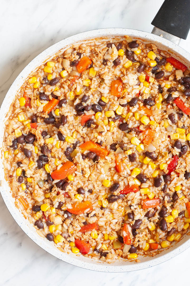A white frying pan with colorful ingredients like black beans, corn, bell pepper strips and rice.