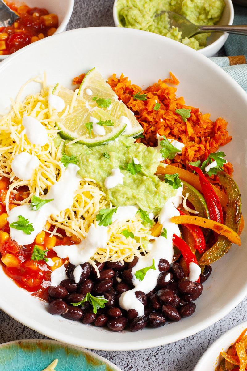 A large white plate in the middle with colorful ingredients like black beans, corn, shredded cheese, bell pepper strips, lime, orange rice. Small white bowl are scattered around with the same ingredients.