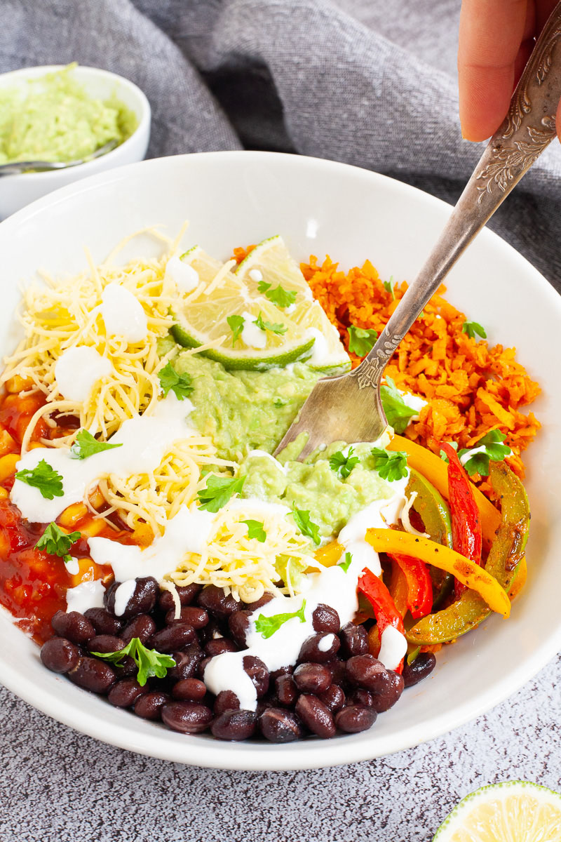 A large white plate in the middle with colorful ingredients like black beans, corn, shredded cheese, bell pepper strips, lime, orange rice. A hand is holding a fork in the middle.