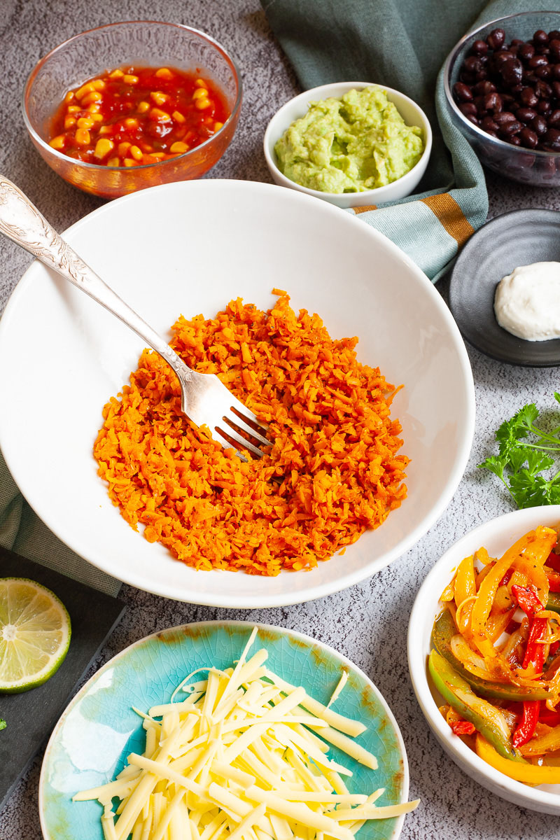 A large white plate in the middle orange riced sweet potato. Small white bowl are scattered around with colorful ingredients like black beans, corn, shredded cheese, bell pepper strips, lime, orange rice.