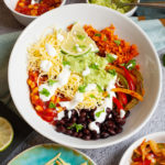 A large white plate in the middle with colorful ingredients like black beans, corn, shredded cheese, bell pepper strips, lime, orange riced sweet potato. Small white bowl are scattered around with the same ingredients.