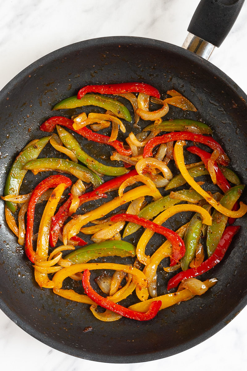 Black frying pan with red yellow green bell pepper strips, and onion slices after frying.