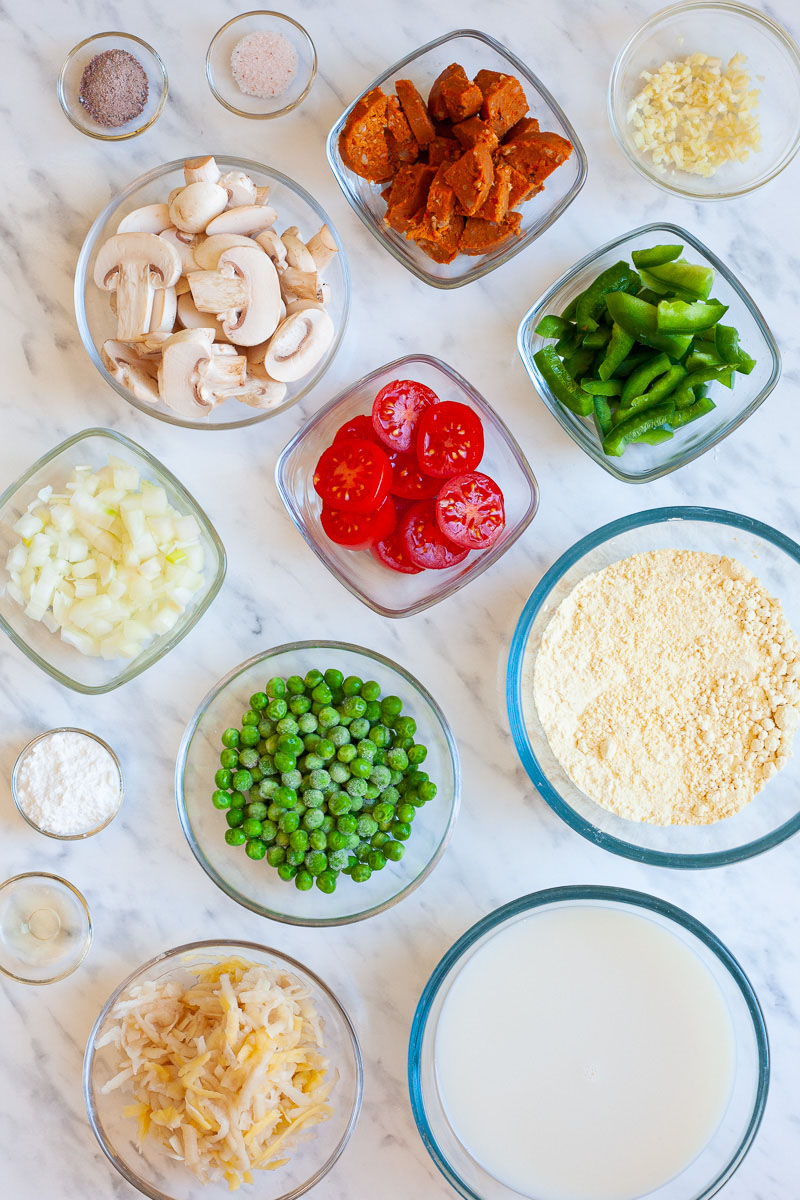 The ingredients of a breakfast casserole is small glass bowls: shredded potato, green peas, chopped onion, chopped garlic, cherry tomatoes, sausage slices, mushroom slices, bell pepper slices, milk, chickpea flour, baking powder, black salt, himalaya salt and apple cider vinegar