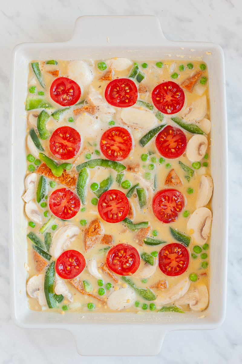A white casserole dish from above from filled with cherry tomato halves, bell pepper slices, green peas, mushroom slices in a yellow liquid