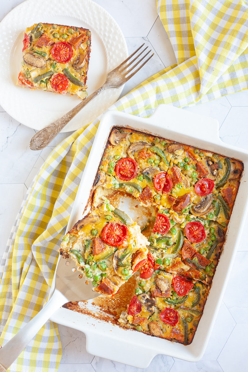 A slice of breakfast casserole with cherry tomatoes, mushroom slices, bell pepper slices on top of a yellow cake-like dough is served on a white plate with a fork. The white casserole dish is in the middle with a slotted turner taking a piece.