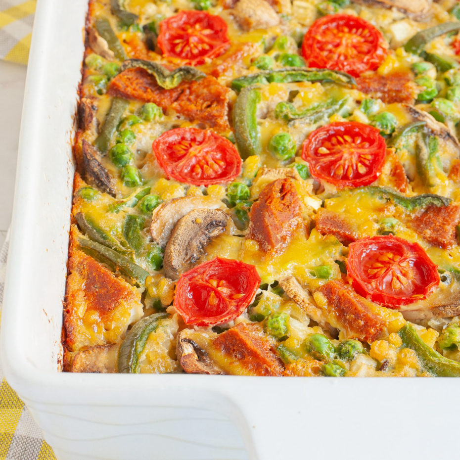 Cherry tomatoes, mushroom slices, bell pepper slices on top of a yellow cake-like dough is in a white casserole dish.