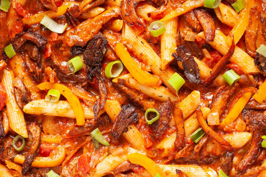 Penne pasta with yellow bell pepper slices, brown mushroom shreds and spring onion rings in a creamy red sauce from above.