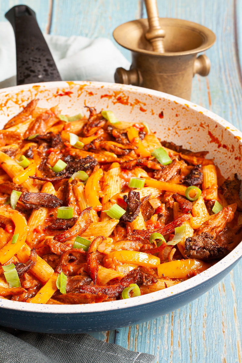 Penne pasta with yellow bell pepper slices, brown mushroom shreds and spring onion rings in a creamy red sauce in a large frying pan