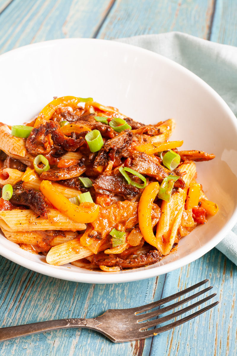 Penne pasta with yellow bell pepper slices, brown mushroom shreds and spring onion rings in a creamy red sauce served in a white bowl. A fork is placing next to the bowl.
