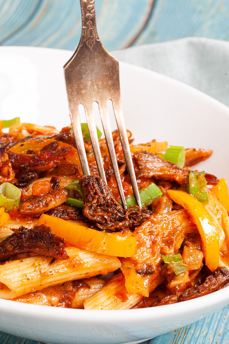 Penne pasta with yellow bell pepper slices, brown mushroom shreds and spring onion rings in a creamy red sauce served in a white bowl. A fork is piercing through the middle.