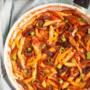 Penne pasta with yellow bell pepper slices, brown mushroom shreds and spring onion rings in a creamy red sauce in a frying pan from above.