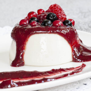 A white plate with white panna cotta topped with a thick purple sauce and different berries up really close.