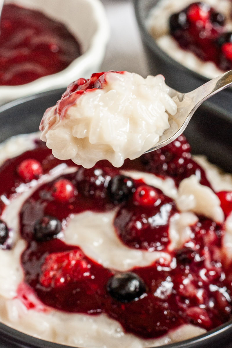 A spoon of creamy white rice pudding. In the background a black bowl with white pudding topped with a swirl of thick red-purple sauce and different berries.