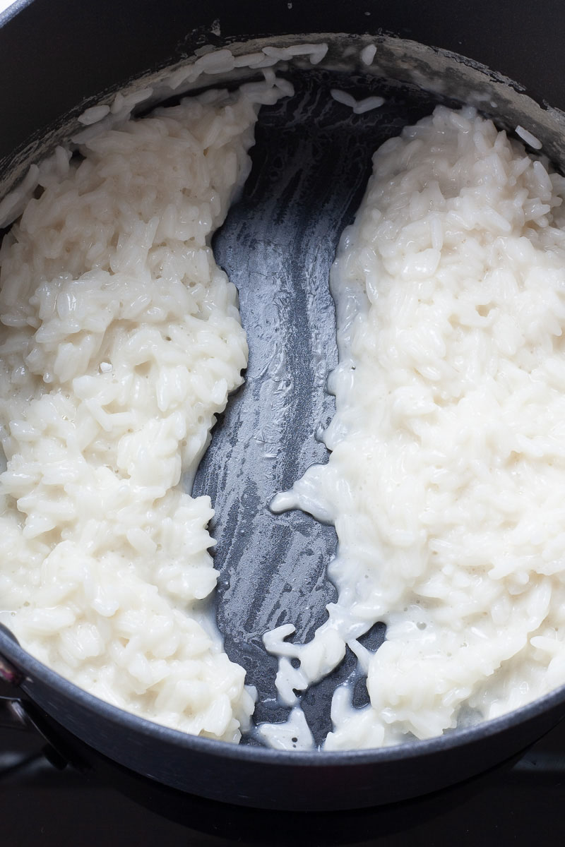 A black saucepan with white creamy rice split in the middle with a draw of a spatula.