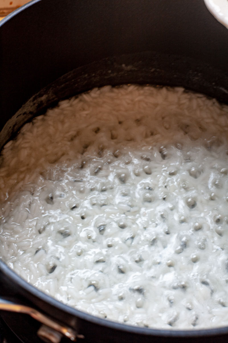 A black saucepan with rice bubbling during cooking