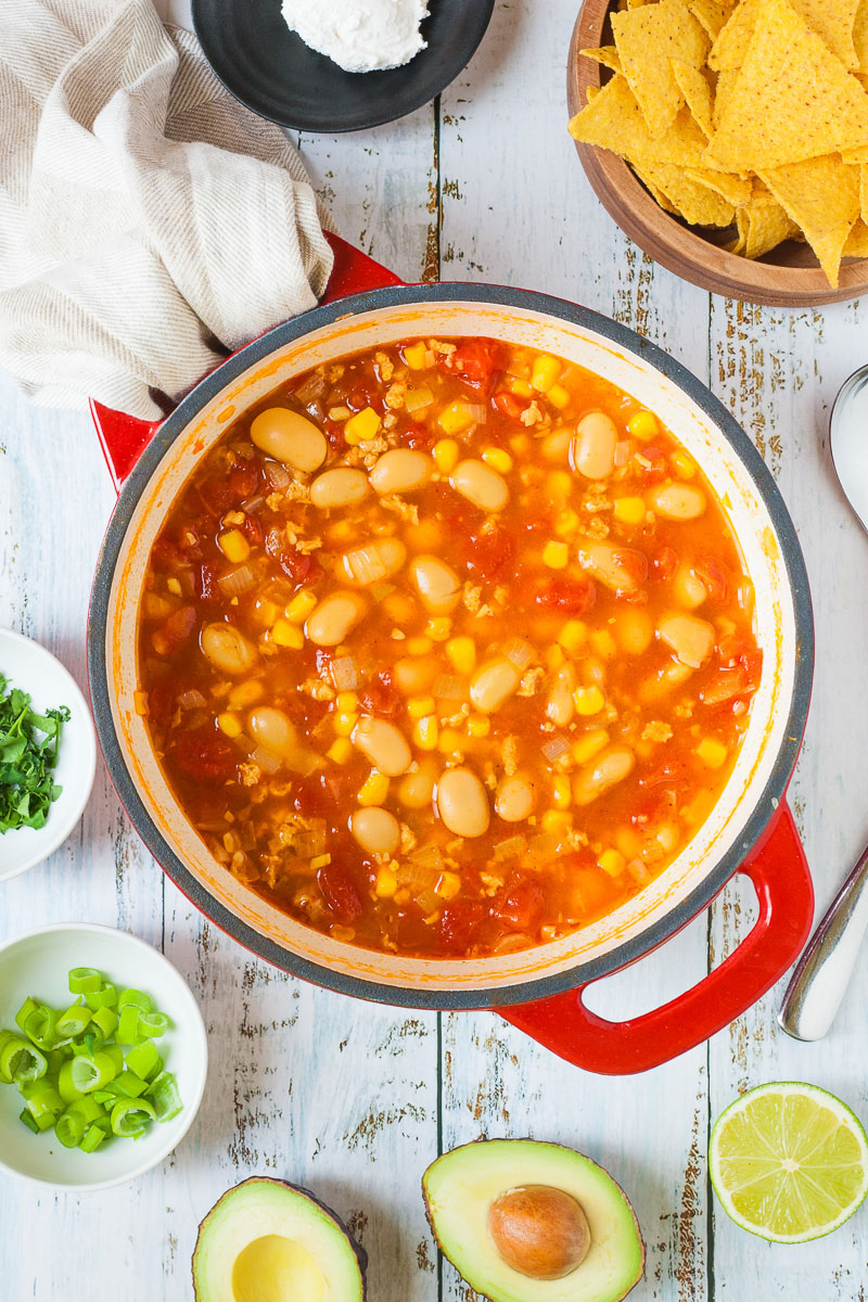 A red Dutch oven is from above with orange soup, white beans, corn, chopped tomato, mince. Half avocado, lime and small bowls of chopped pcilantro and spring onion is around with some tortilla chips and a bit of sour cream on a black plate.