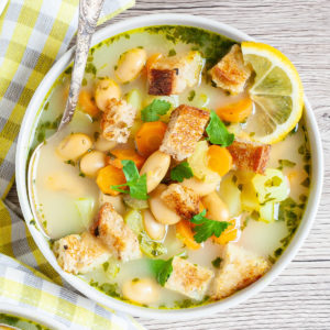 Light yellow soup served in a white bowl with a spoon full of large white beans, croutons, carrot slices, diced potatoes and freshly chopped herbs.