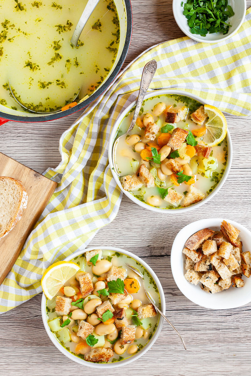 Light yellow soup served in two white bowls full of large white beans, croutons, carrot slices, diced potatoes and freshly chopped herbs. Large pot is in the corner with yellow soup. 2 small bowls with extra croutons and chopped hearbs.