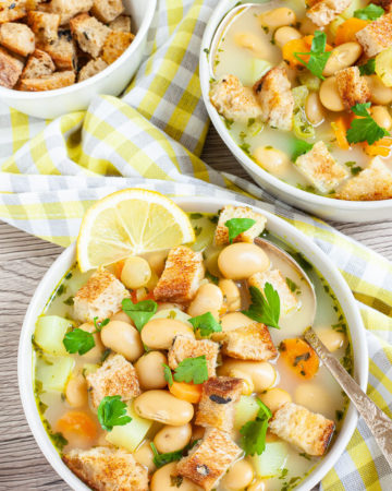Light yellow soup served in two white bowls full of large white beans, croutons, carrot slices, and diced potatoes. It is sprinkled with freshly chopped herbs.